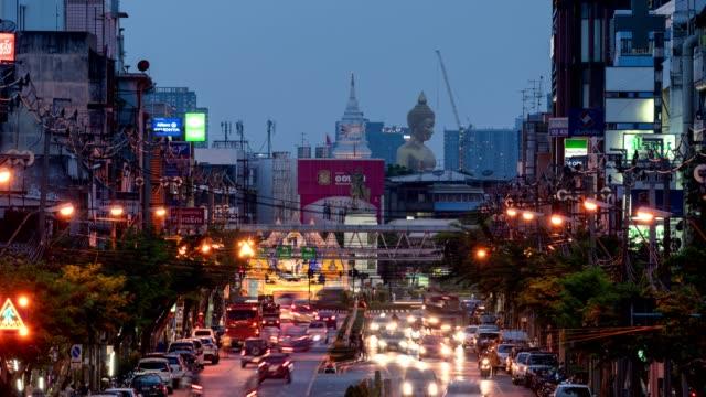 vídeos de stock, filmes e b-roll de paisagem urbana de edifícios com tráfego na estrada e buda grande dourada no centro da noite - religião