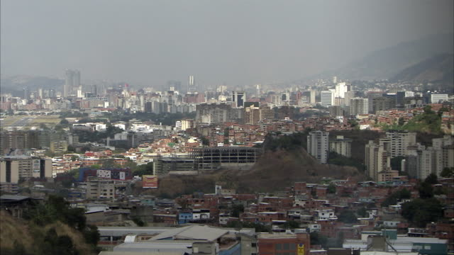 WS PAN HA MS Cityscape of Petare, person hanging laundry by derelict building in foreground / Caracas, Miranda, Venezuela