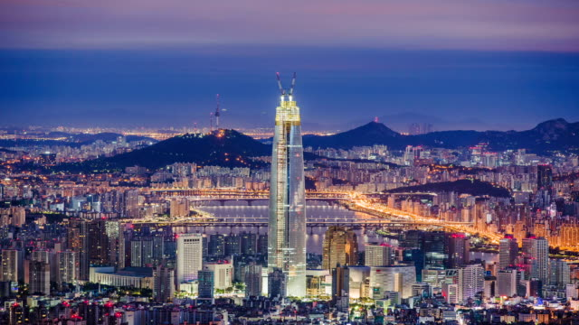 vídeos de stock, filmes e b-roll de cityscape of seoul with lotte world tower and n seoul tower behind it - time lapse da noite para o dia