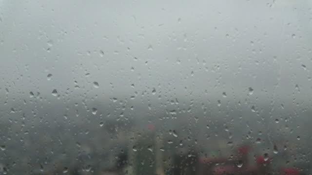 vídeos de stock e filmes b-roll de cityscape through a glass window with raindrops in skyscrapers - nostalgia