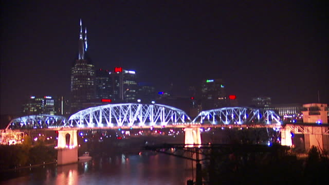 Cityscape PAN to WS Lighted Shelby Street Bridge over Cumberland River pedestrian truss bridge w/ city BG