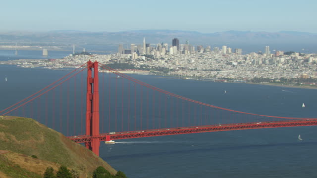 ws tu pov cityscape view with skyscrapers traffic moving on golden gate bridge / san francisco, california, united states - baia di san francisco video stock e b–roll