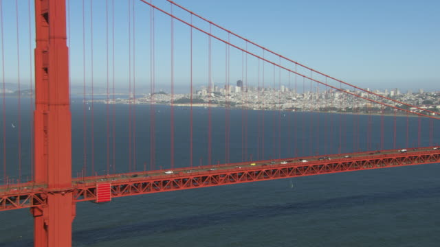 ws zi pov cityscape view with skyscrapers traffic moving on golden gate bridge / san francisco, california, united states - golden gate bridge stock-videos und b-roll-filmmaterial