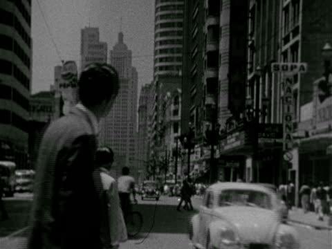 cityscape w/ bridge wide street traffic skyscrapers angled ws street scene w/ pedestrians crossing fg traffic passing down out of frame vs people... - 1966年点の映像素材/bロール