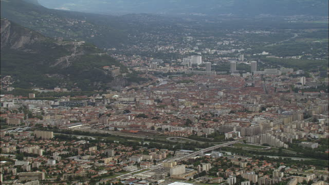 aerial ws zo cityscape with alps in background near communications tower on hill / grenoble, france - grenoble stock-videos und b-roll-filmmaterial