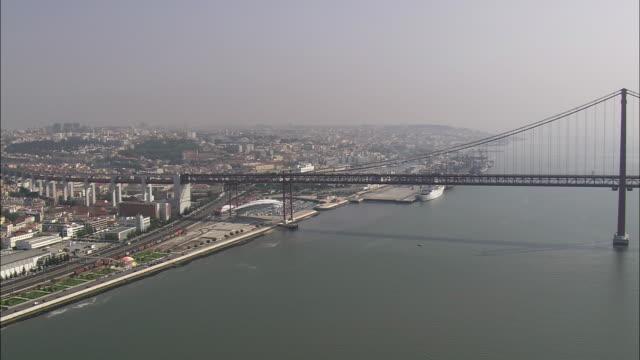 aerial ws cityscape with april 25th bridge over tagus / lisbon, portugal - 4月25日橋点の映像素材/bロール