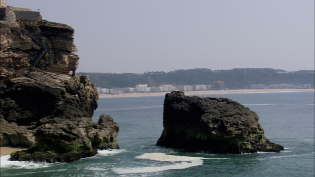 AERIAL WS Cityscape with beach and cliff / Nazare, Leria, Portugal