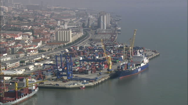 AERIAL WS Cityscape with cargo ship at dock / Lisbon, Portugal