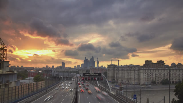 cityscape with dense traffic on a wide urban highway in the foreground and office skyscrapers in the background at sunset - fluchtpunkt stock-videos und b-roll-filmmaterial