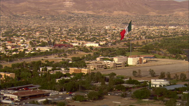 AERIAL ZO Cityscape with Mexican flag in foreground and traffic lined up at border crossing at US/Mexican border, Juarez, Chihuahua, Mexico
