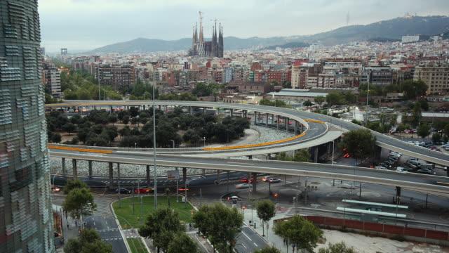 t/l ha ws zo cityscape with placa de les glories catalanes, la sagrada familia in distance, day to night / barcelona, catalonia, spain - barcellona spagna video stock e b–roll