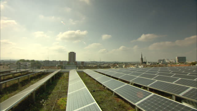 ws pan cityscape with rows of solar panels covering green roof / basel, switzerland - erneuerbarkeit stock-videos und b-roll-filmmaterial