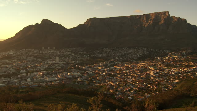 ws ha cityscape with table mountain in background, sunset, cape town, western cape province, south africa - 南ア テーブルマウンテン点の映像素材/bロール