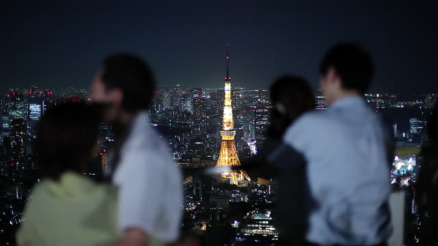 vidéos et rushes de ms shaky cityscape with tokyo tower at night, people in foreground / tokyo, japan - shaky