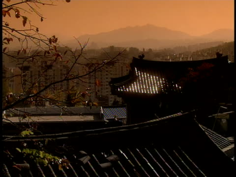 stockvideo's en b-roll-footage met ms, pan, cityscape with traditional korean rooftops in foreground, twilight, seoul, south korea - kleurtoon