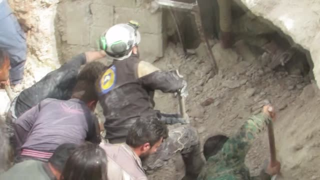 vídeos de stock, filmes e b-roll de civil defence crews and locals conduct search and rescue works after airstrikes hit residential areas of alnaqir village located within a... - ataque aéreo