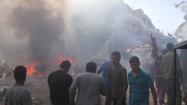 civil defense team members and citizens try to extinguish fire following the airstrike hit a local bazaar in maarrat alnu'man town of idlib syria on... - luftangriff stock-videos und b-roll-filmmaterial