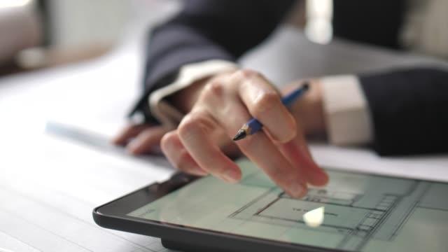 vídeos y material grabado en eventos de stock de ingeniero civil trabajo con tableta computadoras y construcción plan sobre mesa - arquitecto