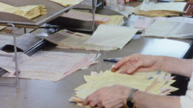MONTAGE Civil Service workers using paper for storing information in ledgers, files, and record books / United Kingdom