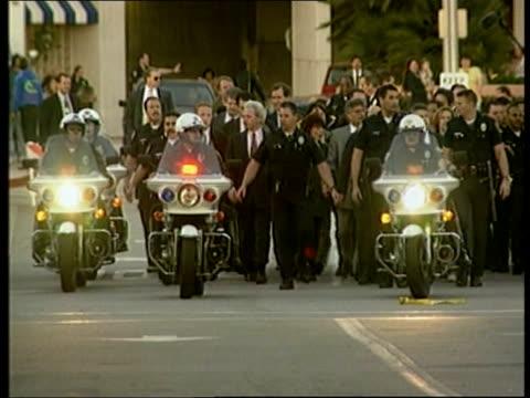 civil trial of o.j. simpson; usa: california: santa monica: police surrounding fred goldman & family as towards: - o・j・シンプソン点の映像素材/bロール