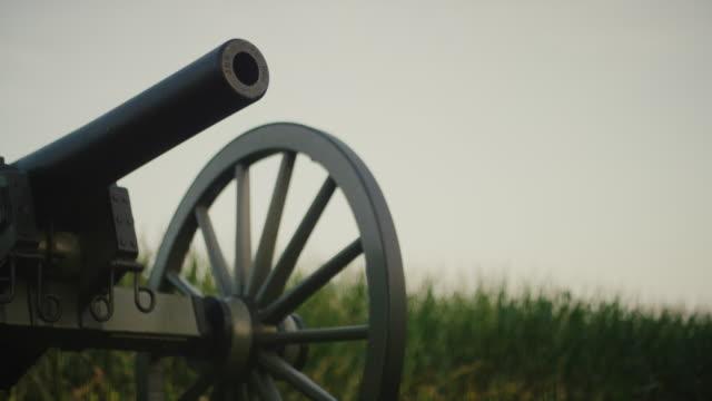 eine us-bürgerkriegskanone aus dem gettysburg national military park, pennsylvania neben einem maisfeld - gettysburg stock-videos und b-roll-filmmaterial