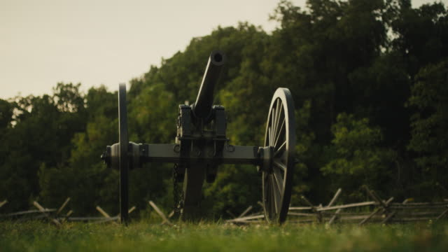 vídeos de stock e filmes b-roll de a us civil war cannon from gettysburg national military park, pennsylvania at sunset in a grassy area next to a forest and a wooden fence - gettysburg