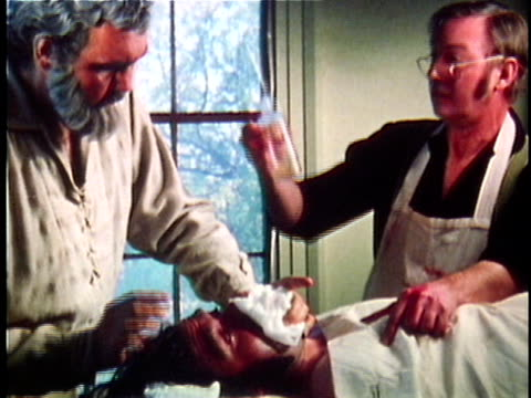 1971 reenactment ms civil war soldier being put under aneasthetic on operating table by two surgeons / 19th century united states / audio - anesthetic stock videos & royalty-free footage