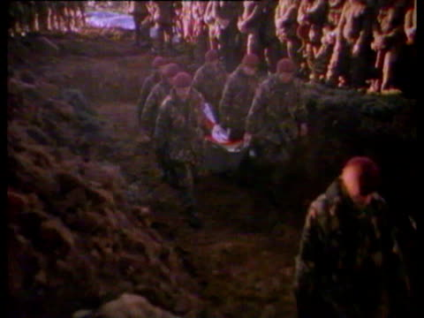 civilian children waving from inside building / dead bodies of soldiers killed covered in tarpaulin lay in grave / soldiers carrying dead body on... - 1982 stock videos & royalty-free footage