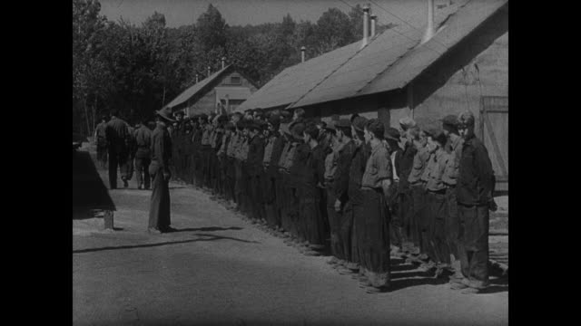 civilian conservation corps standing in camp before army reserve male in uniform possibly roll call young adult males working hard moving rocks... - civilian conservation corps stock-videos und b-roll-filmmaterial