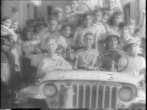 Civilian crowds cheer American liberation troops entering once Facist Palermo / American soldier is driving a jeep loaded down with children through...