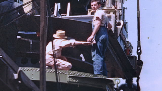 TU Civilian worker directing operator to raise lift platform using hand signal while work is taking place on the USS Yorktown under construction /...