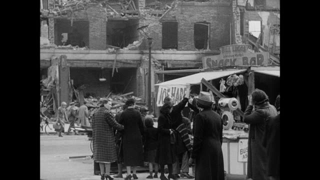 vídeos de stock, filmes e b-roll de montage civilians and air raid workers walking among rubble and police saving a cat / london, england, united kingdom - formato de alta definição