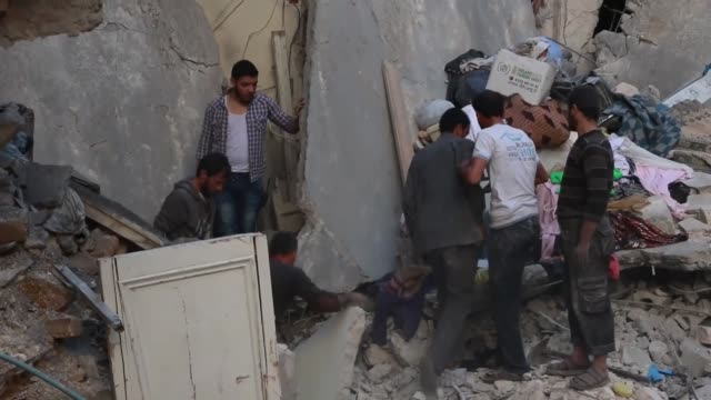 Civilians and civil defense forces try to save people from the wreckage after the Russian airstrikes targeted residential areas at opposition...