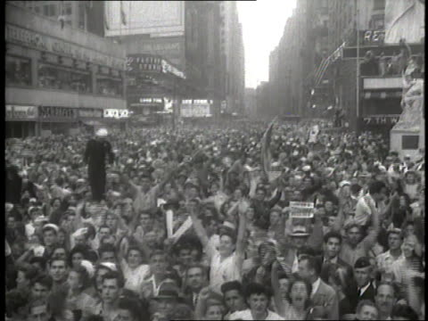civilians and members of the united states military crowd times square to celebrate the japanese surrender on vj day - japanese surrender stock videos and b-roll footage