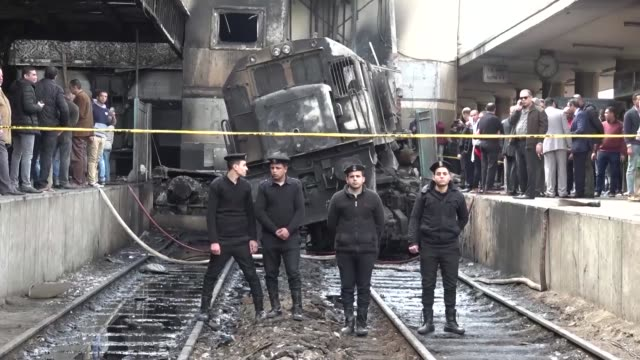 vídeos y material grabado en eventos de stock de civilians and police officers inspect the wreckage after a hurtling train crashed derailed and caught fire at cairo's main station killing at least... - accidente de tren