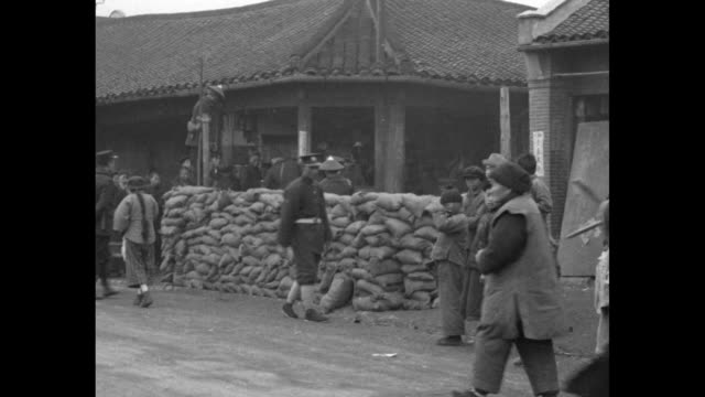 civilians and soldiers fill sand bags, put them in place as barricades around buildings / soldiers pull wooden structure into place, cover it with... - bundle stock videos & royalty-free footage