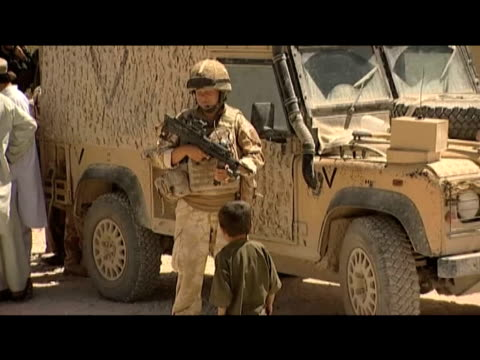civilians and soldiers gather outside reopened school afghanistan 10 september 2009 - 2001年~ アフガニスタン紛争点の映像素材/bロール