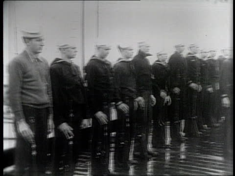 civilians carrying rifles in a line on a dock / officials inspect the men / a man in a trench coat and hat inspects a rifle / boats drive on the... - narrating stock videos & royalty-free footage