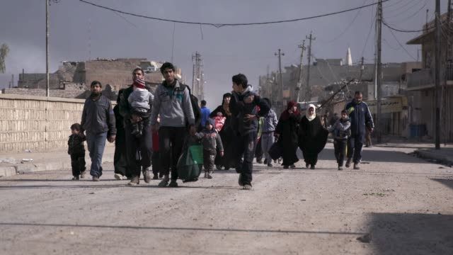 civilians carrying their belongings flee the destroyed city of mosul thousands of civilians have fled the city of mosul due to the war against the... - isis stock videos and b-roll footage