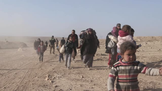 civilians carrying their most valuable belongings flee the city of mosul. thousands of civilians have fled the city of mosul due to the war against... - irak stock-videos und b-roll-filmmaterial