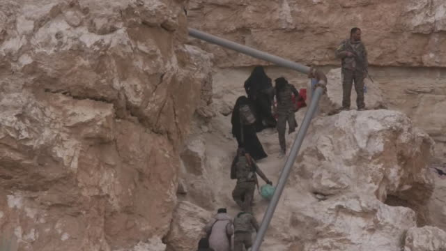 civilians climb up a steep hill to flee an isis-held area of baghouz, syria on march 14, 2019. - (war or terrorism or election or government or illness or news event or speech or politics or politician or conflict or military or extreme weather or business or economy) and not usa stock videos & royalty-free footage