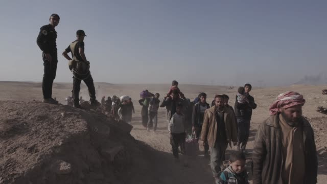 civilians fleeing the city of mosul walk by a makeshift military checkpoint thousands of civilians have fled the city of mosul due to the war against... - isis stock videos and b-roll footage