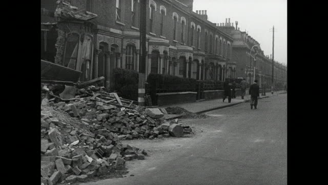 vídeos de stock, filmes e b-roll de montage civilians going to work amidst the rubble and ruin following an air raid / london, england, united kingdom - destruição