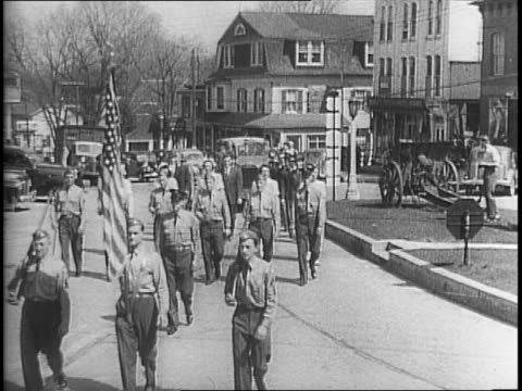Civilians in patriotic street parades in Amenia New York Ontario California and Northport Alabama / men marching with signs / children sitting...