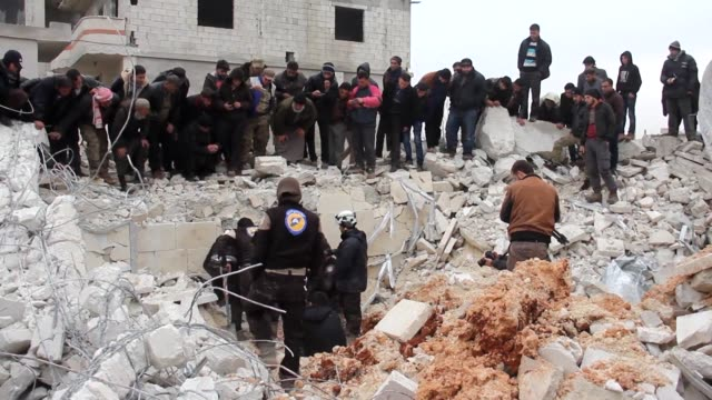 vídeos de stock e filmes b-roll de civilians including members of the civil defense were still searching the rubble friday in the syrian village of al jineh after an air raid hit a... - air raid