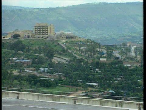 civilians murdered; itn rwanda: kigali: ext tgv view over town as shells explode lms two soldiers rush through long grass l-r - キガリ点の映像素材/bロール