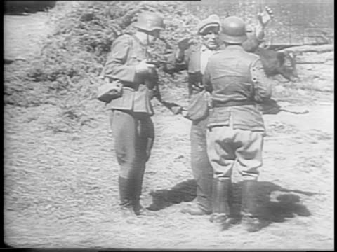 vidéos et rushes de civilians on bicycles searched by german troops / montage of nazis with pistols questioning civilians, burning farmhouse, french currency,... - nazism
