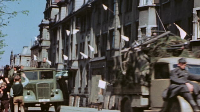 vidéos et rushes de la civilians on sidewalk waving to surrendering german army soldiers driving past in trucks white surrender flags blowing on buildings /... - 1945