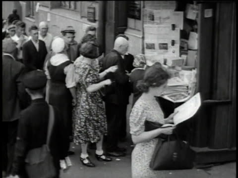 civilians queuing up on street / woman reading paper while other civilians wait / men reading newspaper