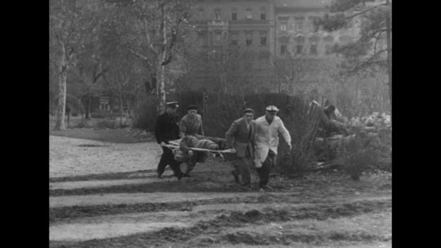 civilians scatter and carry wounded fighters in budapest during the hungarian revolution in 1956. - eastern european culture stock videos & royalty-free footage
